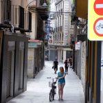 Una noia amb bici, a peu, al carrer Sant Pere