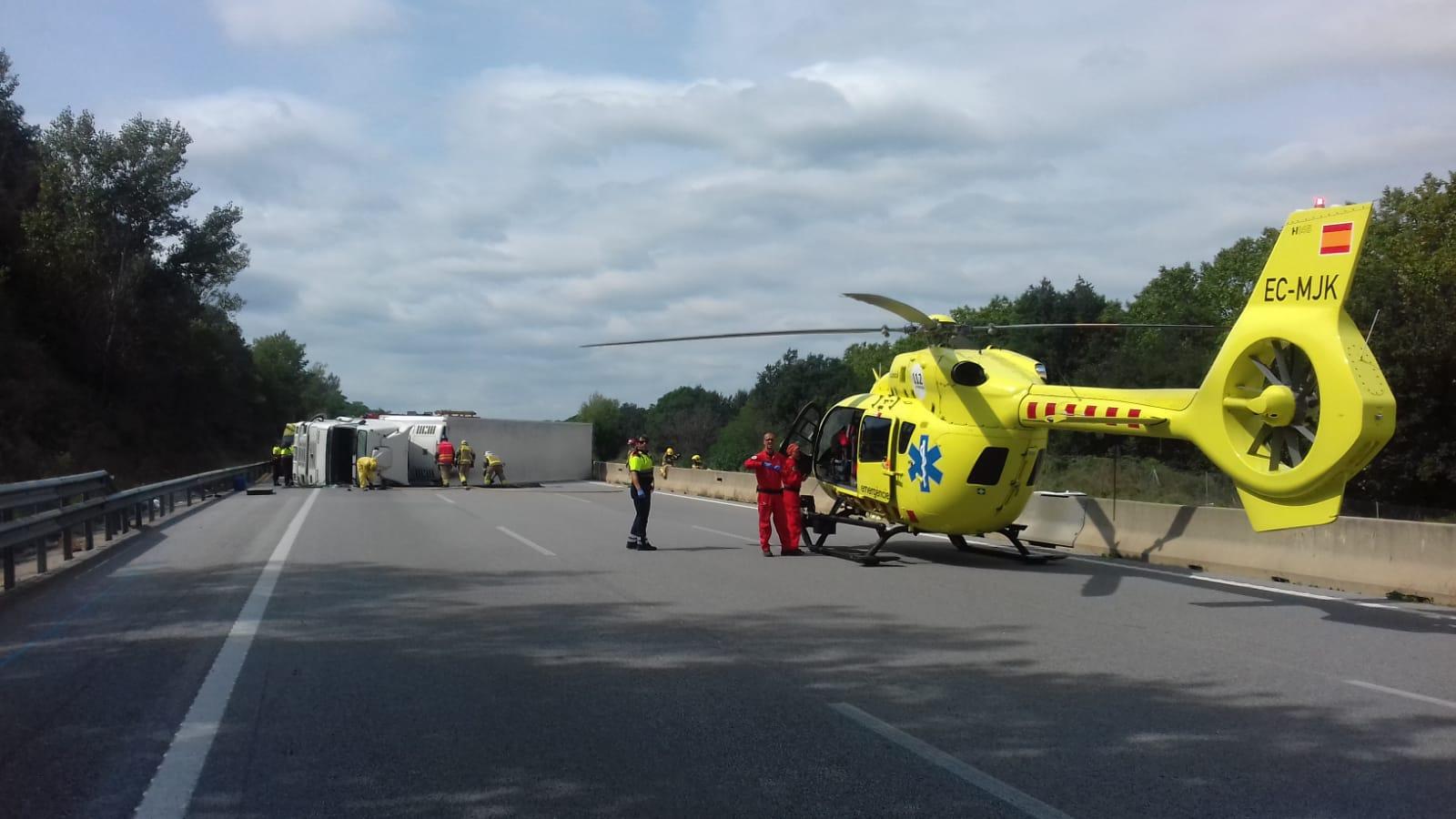 S'ha mobilitzat un helicòpter que ha traslladat al xofer a l'hospital. Al fons, el camió de fruita bolcat