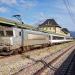 Un tren dels ferrocarrils francesos i un de Rodalies, al fons, a l'estació de La Tor de Querol