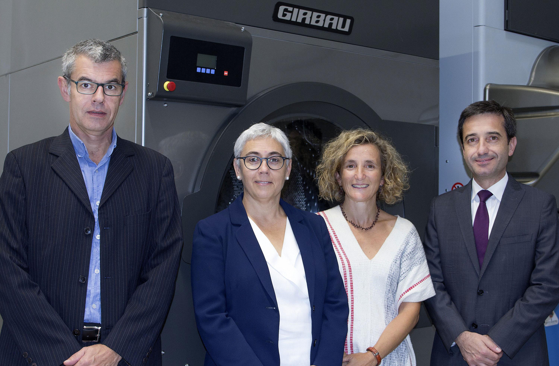 Pere i Mercè Girbau, consellers delegats del grup Girbau, amb Mariona Sanz, responsable d'Innovació, i Guillem Clofent, director general del grup, davant d'una de les màquines de bugaderia que fabriquen