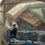 Cinta Vidal pintant el mur 'Refugi' a la cantonada del carrer Catalunya i Muralla