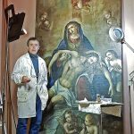Ernest Oms, treballant els últims retocs de la restauració de la tela