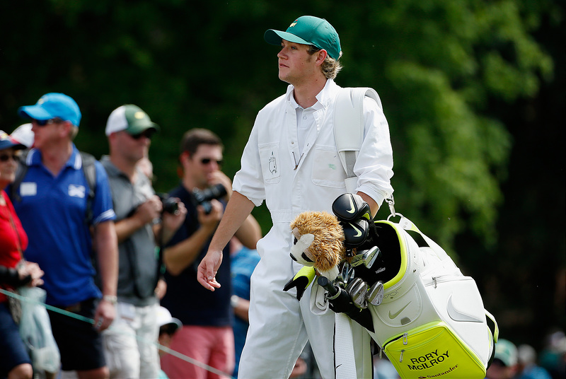 Niall Horan caddies for Rory McIlroy during the Par 3 Contest at the Masters