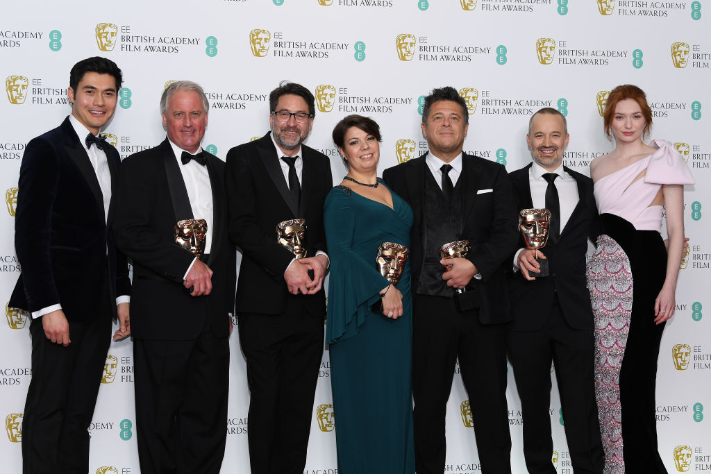 LONDON, ENGLAND - FEBRUARY 10:  (L-R) Presenter Henry Golding, winners of the Sound award for Bohemian Rhapsody, Paul Massey, John Lasau, Nina Hartstone, Tim Cavagin, John Warhurst and presenter Eleanor Tomlinson pose in the press room during the EE British Academy Film Awards at Royal Albert Hall on February 10, 2019 in London, England. (Photo by Pascal Le Segretain/Getty Images)