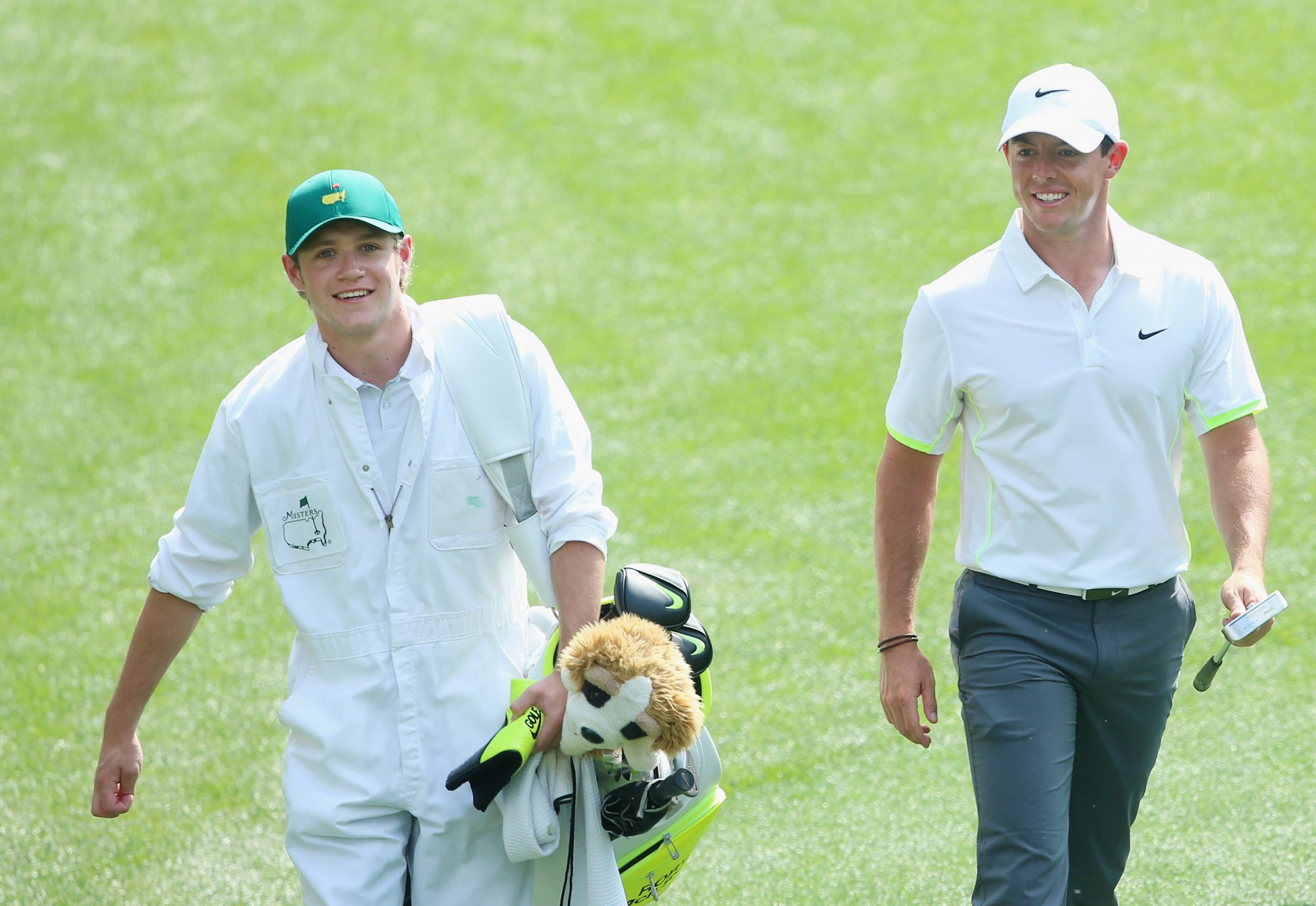 AUGUSTA, GA - APRIL 08:  Rory McIlroy of Northern Ireland walks alongside his caddie Niall Horan of the band One Direction during the Par 3 Contest prior to the start of the 2015 Masters Tournament at Augusta National Golf Club on April 8, 2015 in Augusta, Georgia.  (Photo by Andrew Redington/Getty Images)