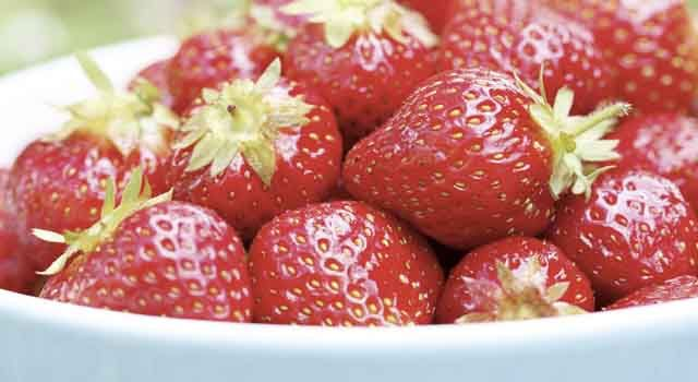 A close-up of fresh strawberries in a light blue bowl resting on a grass surface.