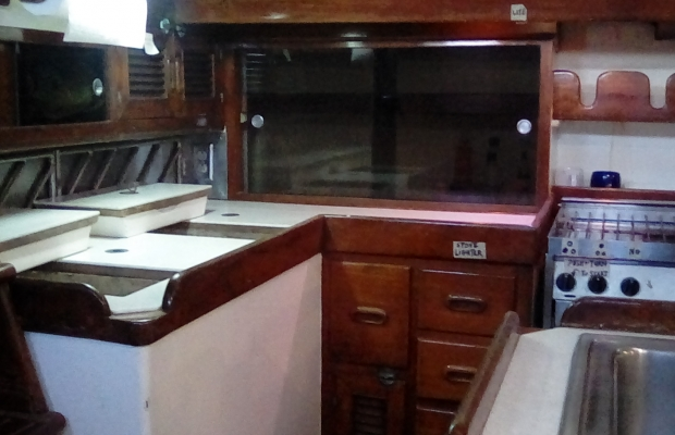 the galley area - refrigerator lids are open, stove is to the right, sink in foreground.