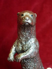 silver standing otter on a naturalistic base.