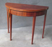 A MAHOGANY DEMILUNE CARD TABLE