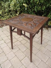 Arts & Crafts carved oak table with dolphins