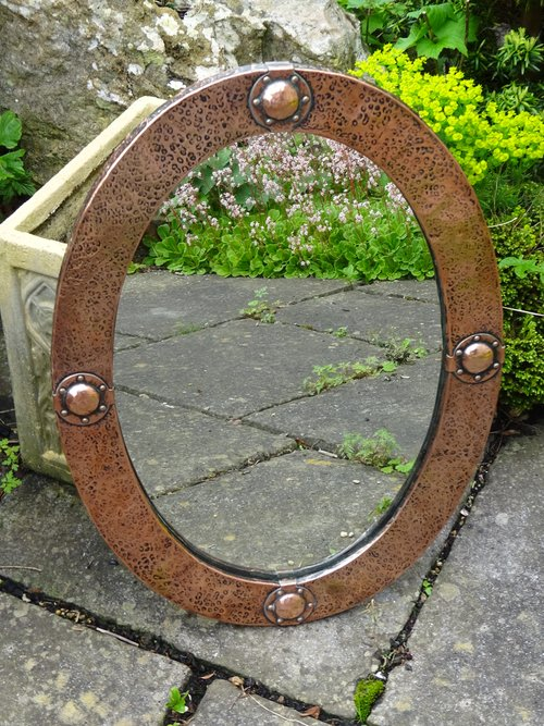 Arts & Crafts copper oval mirror with bosses