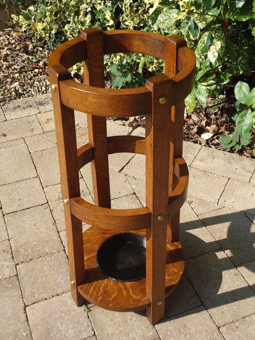 Arts & Crafts oak round stick stand with brass studs