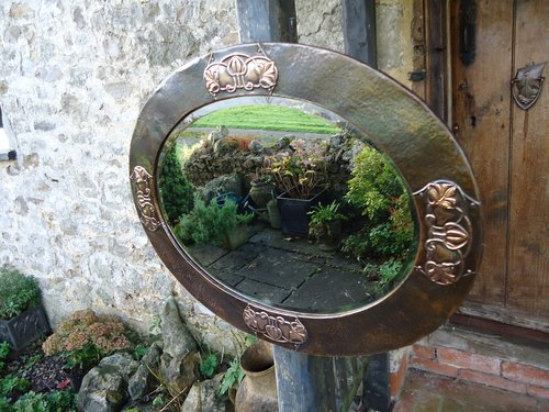 Arts & Crafts oval copper mirror with flowers