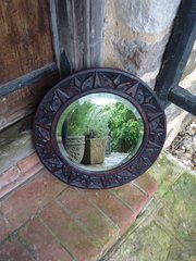 Arts & Crafts round carved bevelled mirror