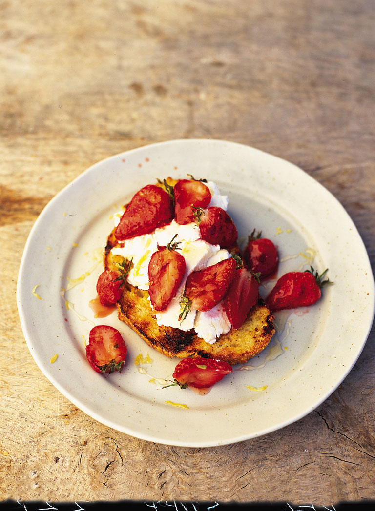 Crumbled ricotta and honey drizzled strawberries sitting on charred eggy bread