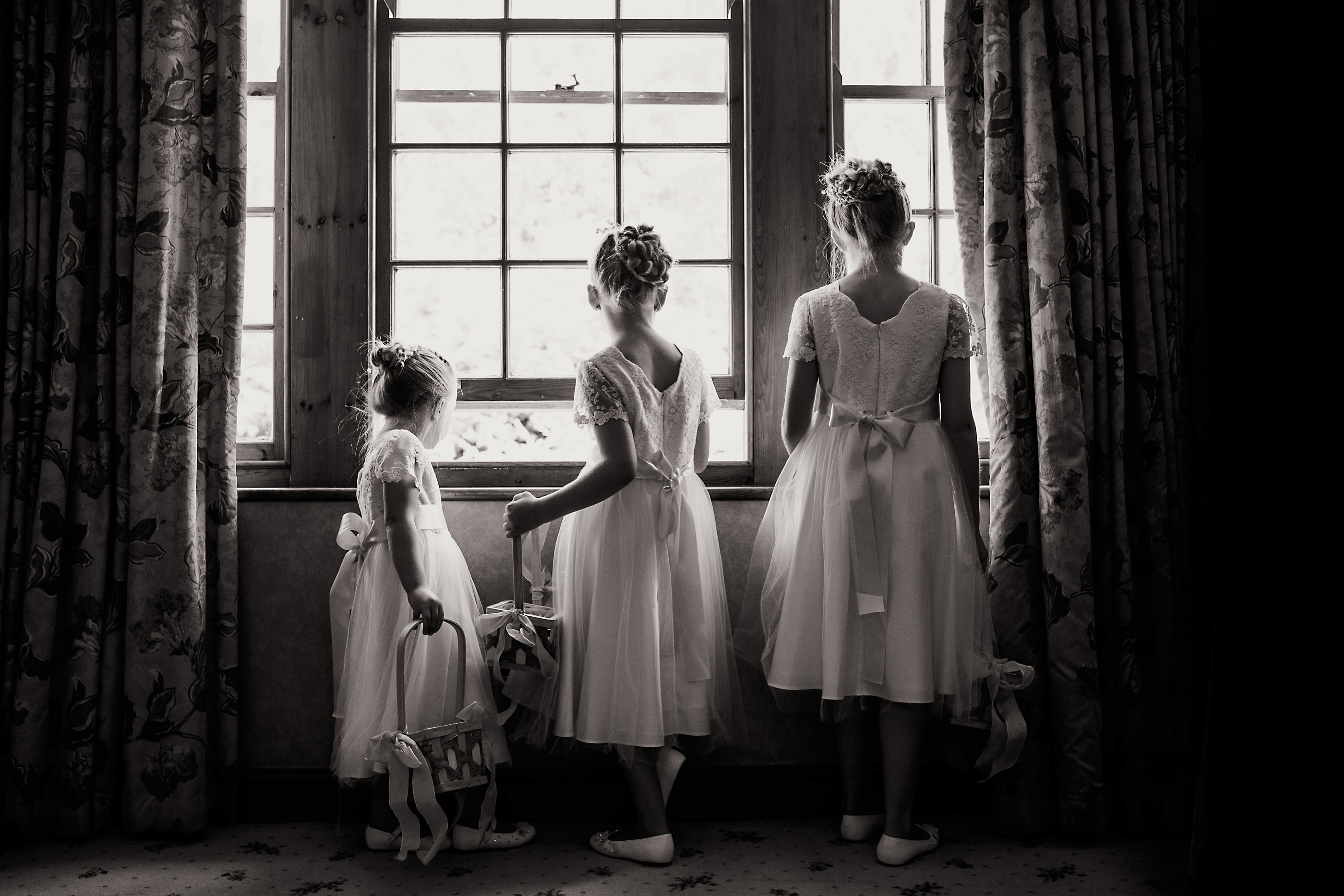 beautiful flowergirls looking out of the window at nunsmere hall