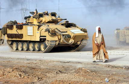 A civilian walks in front of a Warrior Infantry Fighting Vehicle of 1st Battalion, Irish Guards, Iraq, March 2003