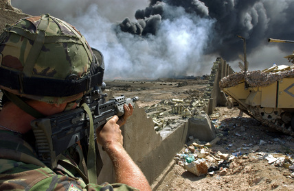 An Irish Guardsman looks for Iraqi enemy positions as Royal Engineers cap one of the burning oil wells, Basra, April 2003