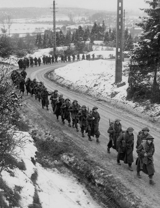 British infantry advancing through the snow, Ardennes, 1945