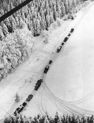 Aerial view of a transport column in the snow, Ardennes, 1945