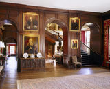 View of the entrance Hall at Antony showing the staircase, three arches , stained oak panelling, paintings and early C18th oak chest