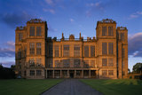 Looking up the path to the exterior of Hardwick Hall, bathed in the golden glow of the setting sun, with blue sky beyond