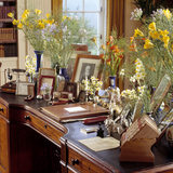 Partial view of the top of the Regency writing table showing photographs, knife box and flowers