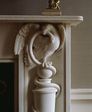 Detail of a white marble fireplace featuring an eagle and snake in the south bedroom at Hinton Ampner
