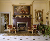 View to porphyry fireplace with Regency giltwood armchairs in the entrance hall at Hinton Ampner