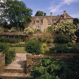 View of the west front of Snowshill Manor seen from the Well Court with flowers and foilage