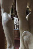 A view through the legs of one sculpture towards the Adonis sculpture by John Edward Carew in the Square Bay in the North Gallery at Petworth House, West Sussex