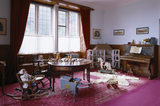 Room view of the Day Nursery including the dolls house, piano, polar bear skin, milk float and table with toys at Lanhydrock