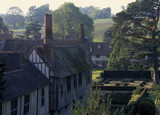 View of half-timbered cottages with gardens, at Ightham Mote