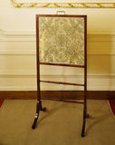 One of a pair of Regency mahogany firescreens with embroidered banner