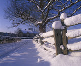 A view of Bateman's down the snow covered drive, with snow piled high on the fencing and gate