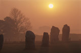 Avebury Stone Circle at Sunrise with misty orange sky and rising sun
