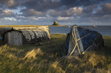 A view over upturned boats towards Lindisfarne Castle, Holy Island, Northumberland