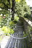 Garden with ornamental bench and plants alongside the River Itchen and C18th Winchester City Mill, Hampshire