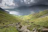 A striking view of walkers on the Scafell path with Wastwater in the distance at Wasdale, Cumbria