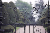 Close up detail of the Chirk Castle gates showing the curved and ornate iron design with the drive way in the distance