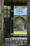 Looking into the Well Court and towards the Venetian well-head and the zodiac clock at Snowshill Manor, Gloucestershire, UK from the garden house