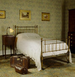 The Larkspur Bedroom at Standen with a bed from Heals, an old leather suitcase and bag and wallpaper by William Morris