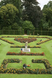 Overall view of formal garden whilst gardeners deadheading the flowers