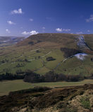 A view of Edale in early spring, snow dusts the side of the hills in shade