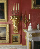 A detailed close up of an ormolu candle branch, a mermaid bracket, and the corner of the fireplace in the Drawing Room