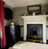 The fireplace in Beatrix Potter's bedroom at Hill Top, Sawrey with a white skin rug on the floor and a red curtain on the window.