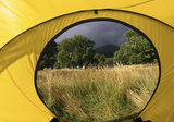 N.T campsite at Wasdale Head, Cumbria, showing grasses in the foreground with tents and trees behind them, seen through the opening of a tent, under the dark sky of a gathering storm.