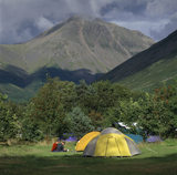 View of the NT Campsite at Wasdale Head with multi-coloured tents, seated visitors, and Cumbrian mountain behind