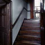 The staircase up to the half-landing, and oak mullion window at Hill Top, the home of Beatrix Potter in Sawrey, Cumbria