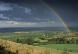 A long distance view over the sun bathed fields of the Clent Hills, Hereford & Worcester, to the dark stormy sky on the horizon with a rainbow streaking across it